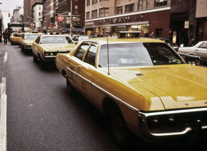 Lineup of yellow cabs (led by a Dodge Polara) seeking fares on Lexington avenue and 61st Street in 1973 by Dan McCoy